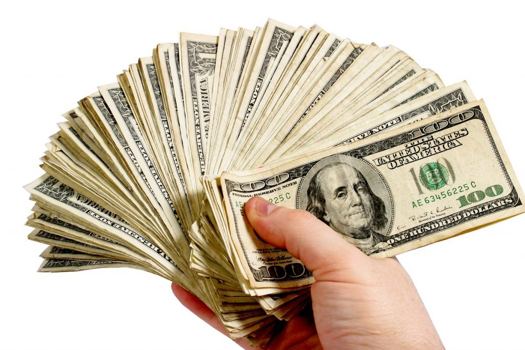 holding money 1024x683 - How To Balance Your Budget To Pay For BJJ Training